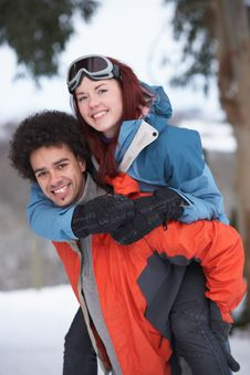 Teenage Boy Giving Girl Piggyback In Snow Royalty Free Stock Image