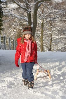 Free Young Girl Pulling Sledge Through Snowy Landscape Stock Images - 14189024