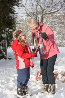 Free Young Girl Showing Grandmother Icicle In Snowy Lan Stock Photography - 14189032