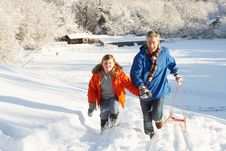 Free Father And Son Pulling Sledge Up Snowy Hill Stock Photos - 14189083