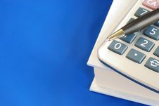 Free Pen And Calculator On The Book Isolated On Blue Stock Photography - 14189862