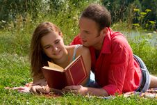 Free Smiling Couple Reading And Relaxing At The Park. Royalty Free Stock Photos - 14238358