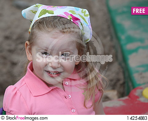 Free Cute Girl Smiling In Sandbox With A Scarf On Head Stock Photos - 14254883