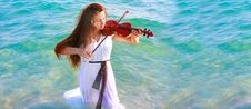 Young Woman Playing Violin In Water Stock Image