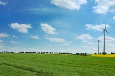 Wind Turbines Among Rapeseed Field And Meadows Stock Photo