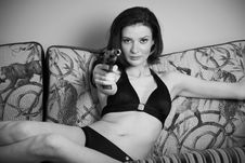 Free Young Attractive Female With A Gun On A Couch Royalty Free Stock Images - 14273999