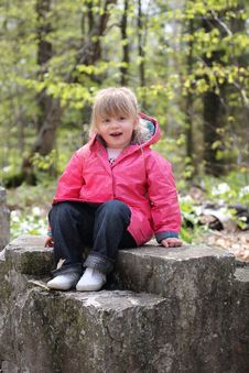 Free Happy Little Girl Sitting On Rock Stock Image - 14285711