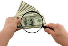 Dollar Bills And A Magnifying Glass In Hand Royalty Free Stock Images