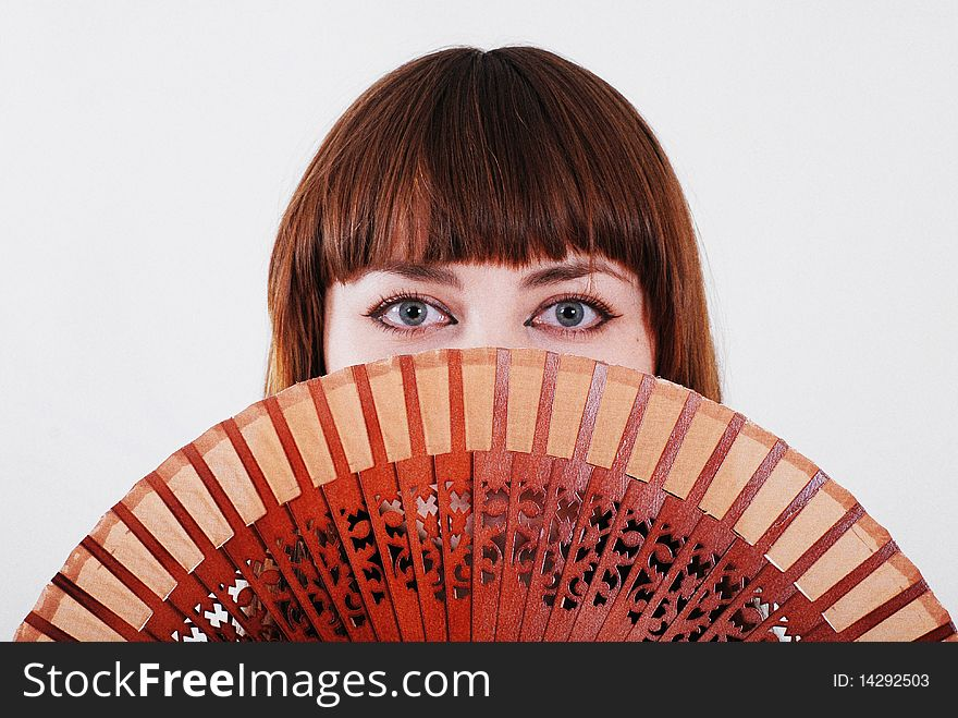 Young woman looking through a hand fan.