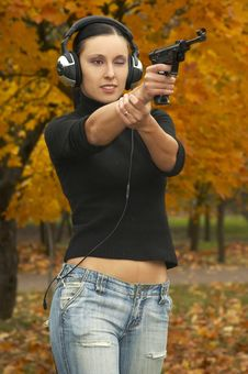 Girl  Brunette In  Headphones With  Pistol Royalty Free Stock Photo