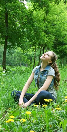 Happy Young Girl Sitting On The Grass Stock Photos