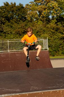 Boy Rides Scooter In A Pipe At A Skate Park Royalty Free Stock Images
