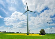 Free Wind Turbines Among Rapeseed Fields And Meadows Royalty Free Stock Images - 14324349