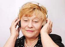 Old Woman Listens To Music Stock Photo