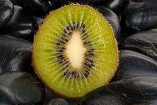 Half Kiwi On Dark Stones Stock Photography