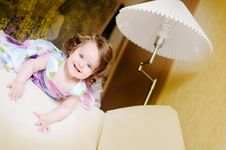 Free Girl On Sofa Near Lampshade Royalty Free Stock Images - 14349169