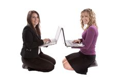 Two Women With Laptops Back To Back Royalty Free Stock Photography