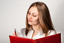 Pretty Young Woman Writing In Notice Book Royalty Free Stock Image