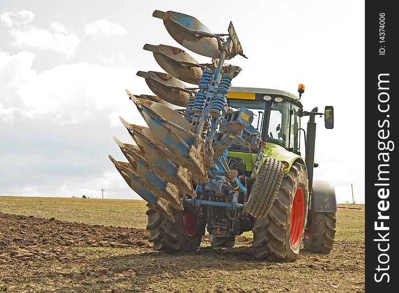 Tractor turning with a raised plow.