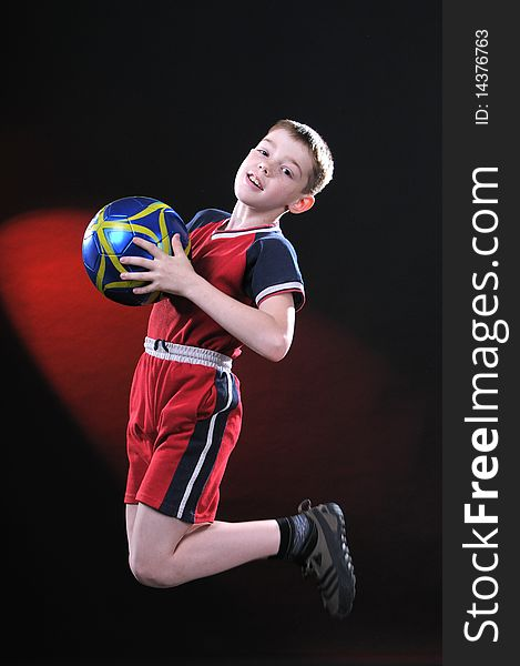 Boy in jump catches a soccer ball