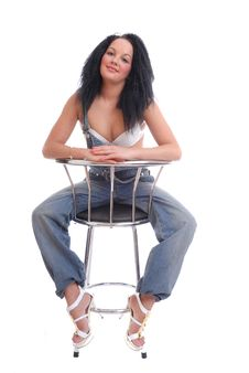Pretty Girl In Bra And Dungarees On Stool Royalty Free Stock Photo