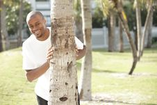 Free Man Smiling From Behind A Tree Stock Image - 14428271