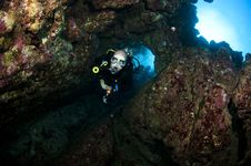 Scuba Diver Swimms Through A Hole In The Wall Stock Photo
