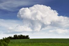 Green Meadow With Huge Clouds Stock Image