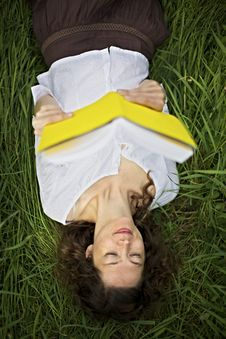 Girl Lying In Meadow Reading Royalty Free Stock Images