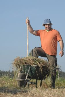 Free Farmer Finish Loading Wheelbarrow With A Haystack Royalty Free Stock Images - 14450559