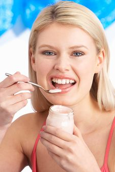 Young Woman Eating Yoghurt In Studio Royalty Free Stock Photos