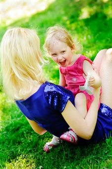 Girl Sits On Her Mother S Knees On A Green Lawn Stock Image
