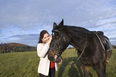 Equestrienne  Strokes A Horse. Stock Photo