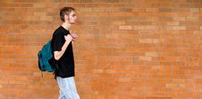 Free Student Walking Besides Brick Wall Royalty Free Stock Photography - 14487187