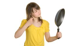 Girl Looks In Reflexion At Bottom Of Frying Pan Royalty Free Stock Photos