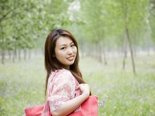 Free Cheerful Asian Woman Carrying Shopping Bag Royalty Free Stock Images - 14569679