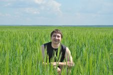 Free A Man Sits In A Field Of Green Wheat Stock Image - 14576921