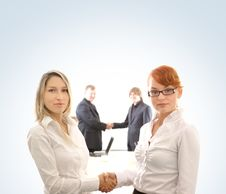 Two Business Women In Front Of Two Men Stock Photo