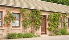 Cottage With Roses Round The Door. Stock Images