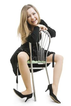The Cheerful Woman Sits Astride A Chair Stock Photo