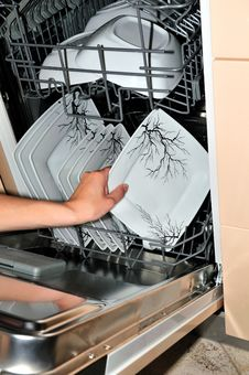 Taking Plate From A Dishwasher Royalty Free Stock Image
