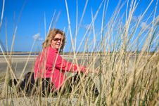 Woman Sitting In The Sand Dunes On The Beach Stock Photography