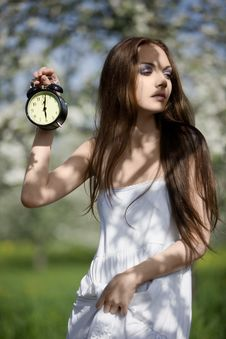 Young Girl With An Alarm Clock In The Meadow Stock Photography