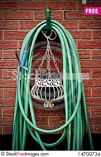 Coiled Garden Hose Hanging on Brick Wal Stock Photo