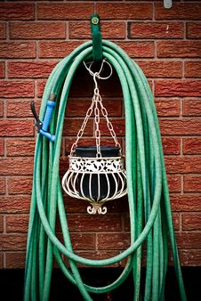 Coiled Garden Hose Hanging On Brick Wal Stock Images
