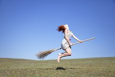 Free Young Red-haired Witch On Broom Flying Over Green Stock Photos - 14720213