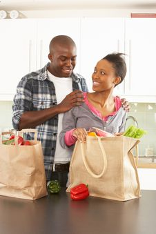 Free Young Couple Unpacking Shopping In Kitchen Stock Image - 14720531
