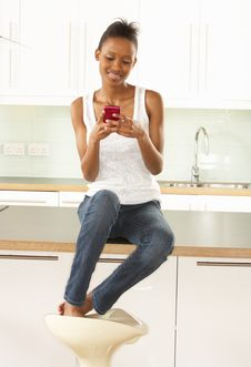 Free Woman Using Mobile Phone Sitting In Kitchen Royalty Free Stock Photography - 14722967