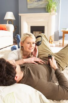 Couple Listening To MP3 Player Laying On Stock Photos