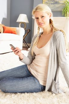 Free Woman Using Mobile Phone Relaxing Sitting On Rug Stock Photography - 14725802